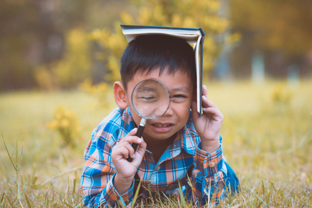 Asian boy exploring the environment with a magnifying glass.