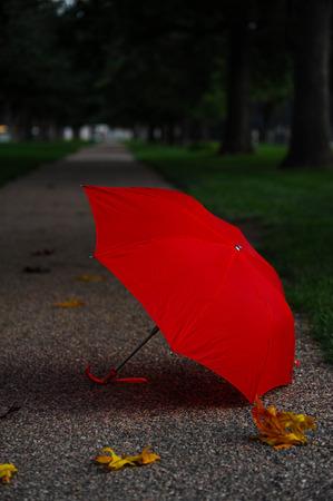 Red umbrella on sidewalk Imagens