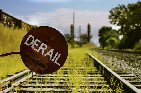 derail: Derailer sign over train tracks with green grass and industrial complex in background