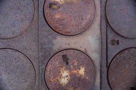 Six metal, round burner covers on pioneer, wood burning stove Imagens