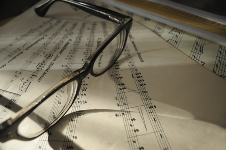 Pair of black glasses on music sheet with notes Imagens
