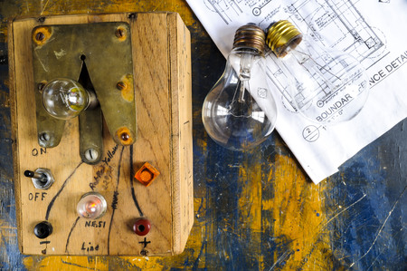 burned out: Homemade lightbulb tester with two lightbulbs on paint splattered work table