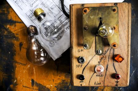 Homemade lightbulb tester with two lightbulbs on paint splattered work table