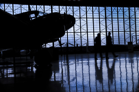 multiples: Silhouette of prop airplane in hanger with blue clouds and two mechanics