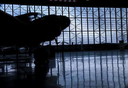 Silhouette of prop airplane hanger with blue clouds in background