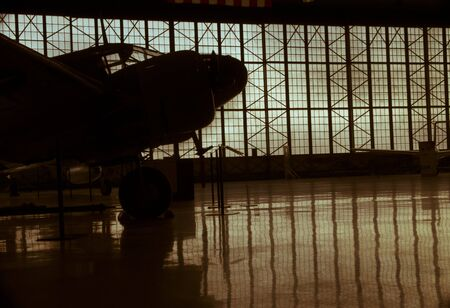 Silhoutte of prop airplane in hanger with reflection and metallic clouds in background