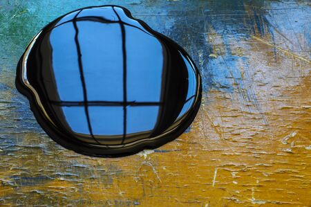 refelction: Black paint spil on orange and blue table with window refelction