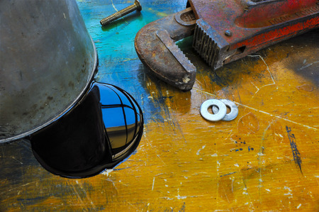 Oil can, soill, monkey wrench on orange and blue work table Imagens