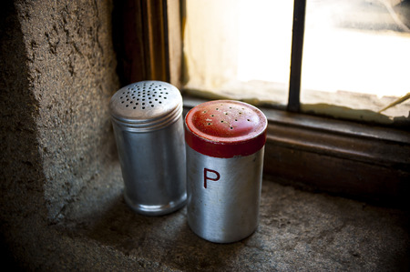 Salt and pepper shaker with red top on windowsill