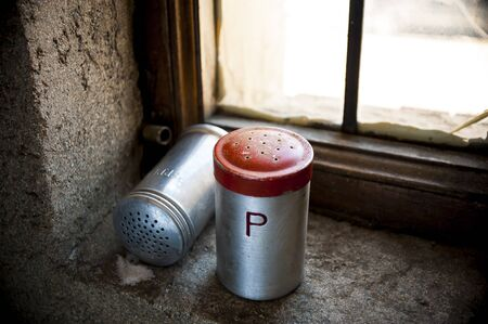 country living: Salt and pepper shaker with red top on windowsill and spilled salt Stock Photo