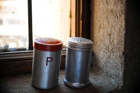 windowsill: Salt and pepper shaker with red top on windowsill