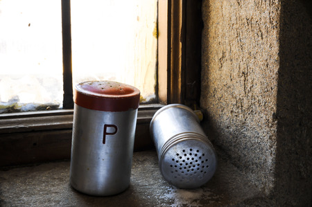 Salt and pepper shaker with red top on windowsill and spill salt