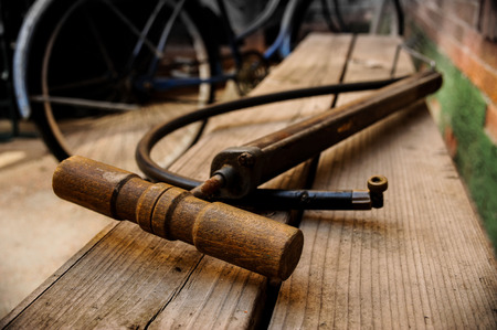 old school bike: Bicycle Pump on Wood Bench with Blue Bicycele in Background Stock Photo