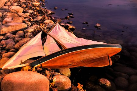 beached: Toy Boat Beached on Rocks in Golden Light Stock Photo