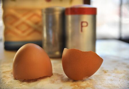 Two Brown Eggs Shells on Flour Next to Pepper Shaker Imagens - 56474555