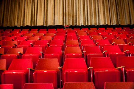 Rows of Red Seats in Cinema with GoldYellow Curtain