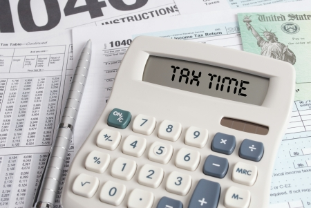 income tax: Tax Forms and Check with Calculator that spells out TAX TIME on the display