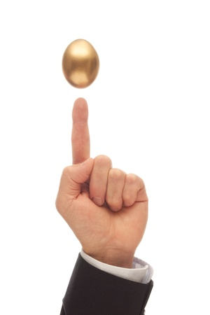 Golden Egg Suspended Above a Hand with the Index Finger Pointing Up Stock Photo - 20916356