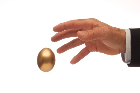 Man s Hand Reaching for the Golden Egg Stock Photo - 20916361