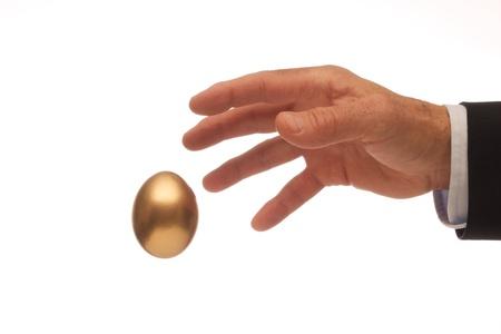 Man s Hand Reaching for the Golden Egg Stock Photo - 20916361