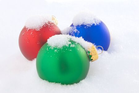 Three Christmas Ornaments Laying in Fresh Snow