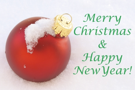 Red Christmas Ornament in Fresh Snow with Merry Christmas   Happy New Year copy text