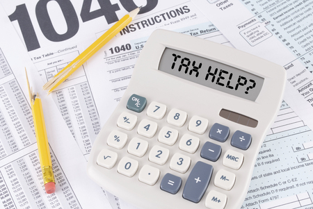 help: Tax Forms and Broken Pencil with a Calculator that spells out TAX HELP  on the display Stock Photo