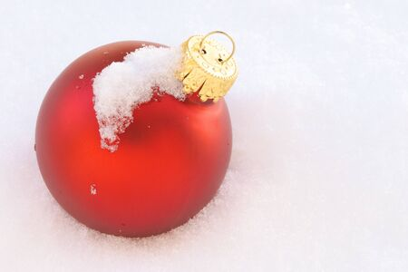 One Red Christmas Ornament Laying in Snow