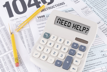Tax Forms and Broken Pencil with a Calculator that has NEED HELP  spelled out on the display Stock Photo