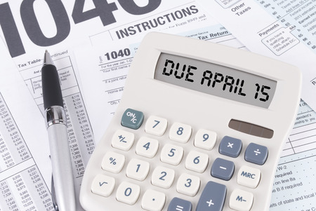 Tax Forms and Pen with a Calculator that spells out DUE APRIL 15 on the display