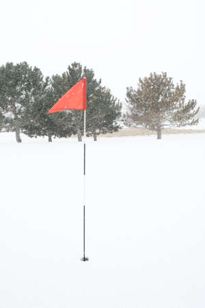 Golf Pin Red Flag Blowing in the Wind and Snow Stock Photo