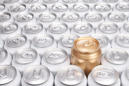 One Raised Gold Can Among a Group of Aluminum Beverage Cans Stock Photo