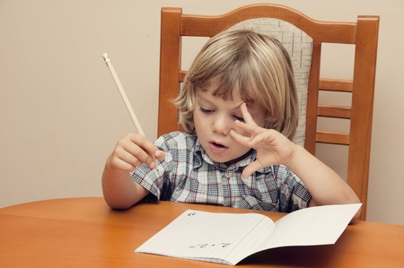 Blond boy with plaid shirt writes in a notebook