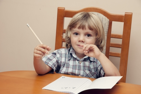 Blond  boy with plaid shirt writes in a notebook photo