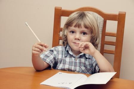chemise carreaux: Gar�on blond avec chemise � carreaux �crit dans un cahier Banque d'images