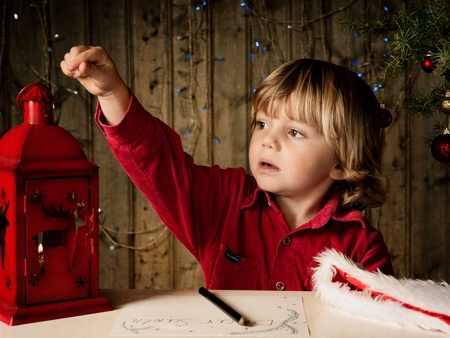 elementary age boy: Blond boy writes a letter to Santa