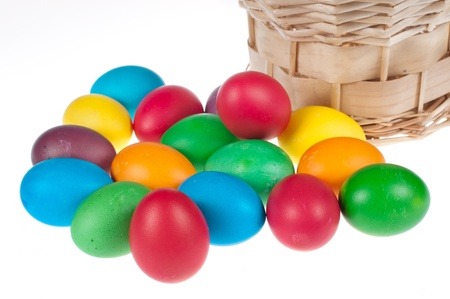Easter eggs and light brown basket on a white backgroung