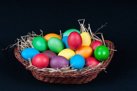 Easter eggs and light brown basket on a black backgroung Stock Photo - 11941724