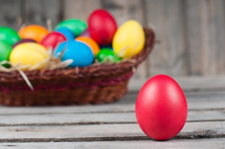 Easter eggs in  brown pannier - one egg is out, selective focus on a red egg photo