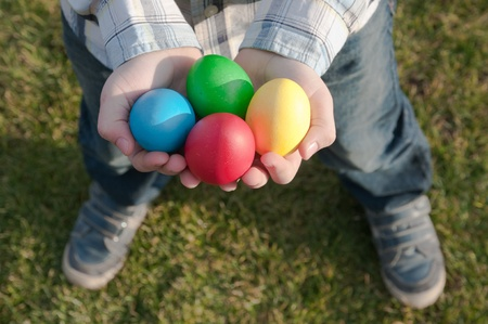 child holding four colored Easter eggs photo