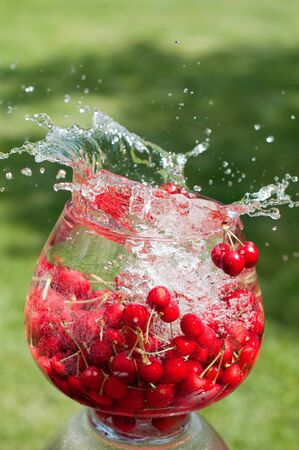 Cherry in a glass and a splash of water photo