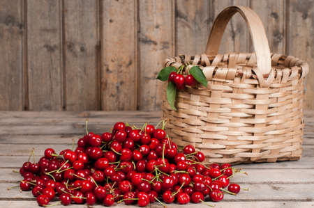 Cherries in a basket on an old wood background photo