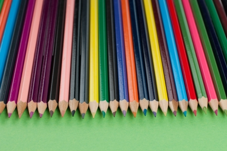 Colored pencils arranged in a row on a green background photo