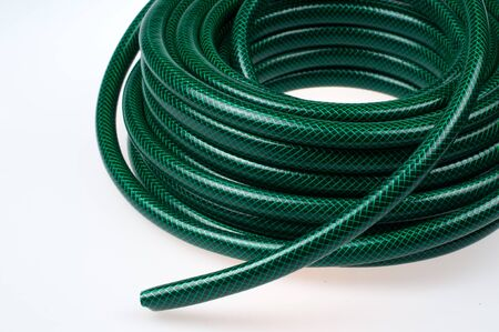 Green hose pipe on white background- selective focus on the front Stock Photo - 18244465