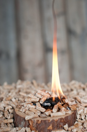 Pine pellets on wooden slice in flames- selective focus on foreground