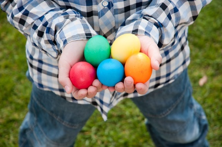 Different color Easter Eggs in a childs hands- egg hunt photo