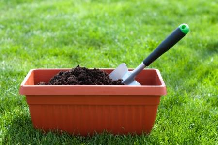 Garden shovel in a pot with compost