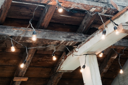 Electrically illuminated light bulbs hanging on old wooden ceiling
