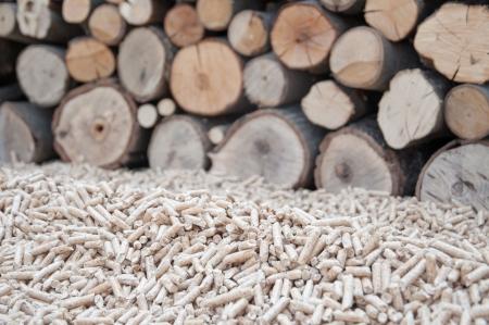Pine pellets infront apile of fire wood Standard-Bild