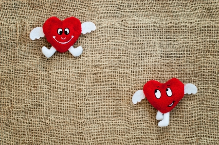 Two Red Hearts of cloth lying on sacking